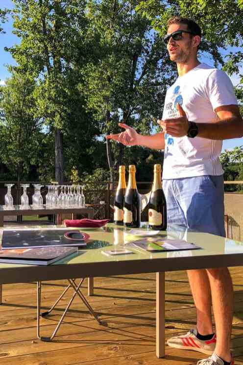 Man presenting three bottles of sparkling wine on a table