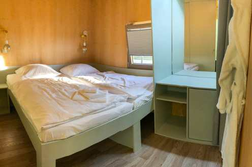 Room in the Big Berry house with a double bed and a sideboard and mirror