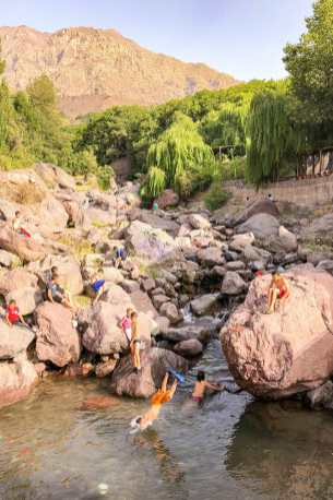 Children playing in a shallow river and jumping in the water from boulders