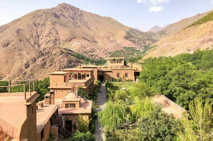 View of the Kasbah du Toubkal from the terrace with a green courtyard garden and the mountains in the background
