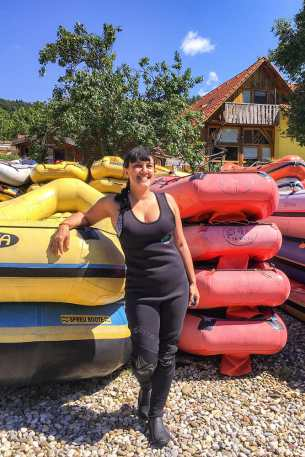 Me standing next to a pile of yellow and red rafts
