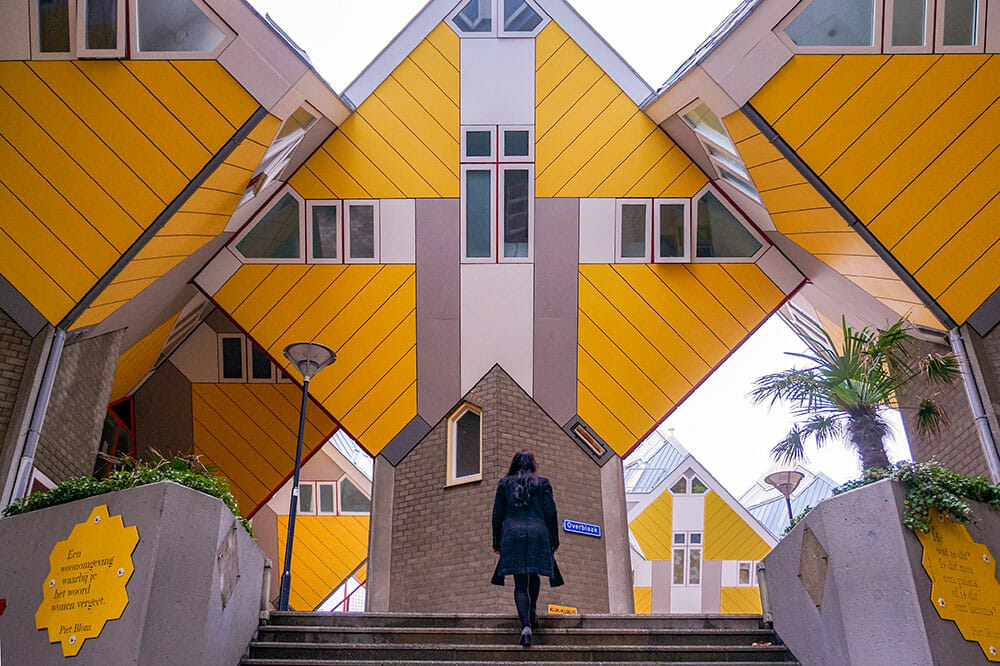 Walking up the steps towards yellow cube shaped buildings