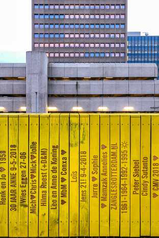 Yellow wooden planks with carved names and building in the background