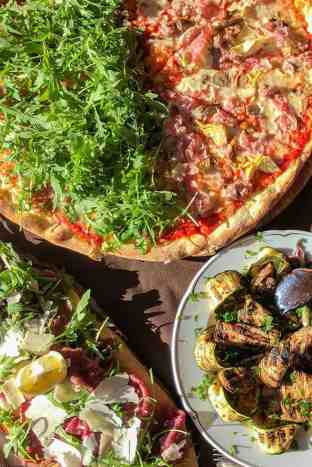 Roasted vegetables and a pizza with rocket on one half and ham on the other