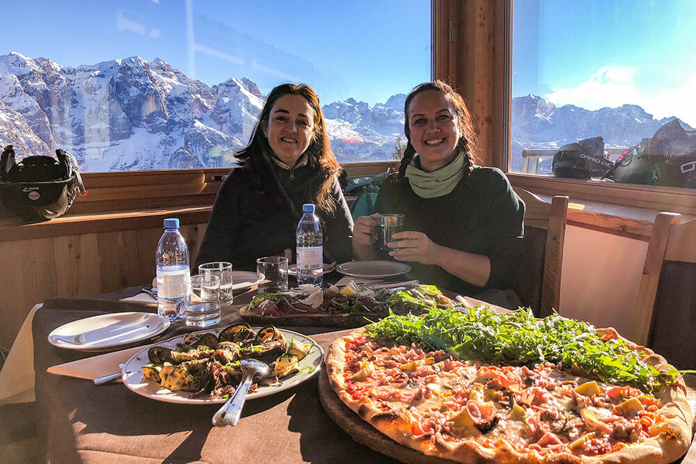 Sitting at a table with a plate of roasted vegetables and a giant pizza with a view of the mountains behind us