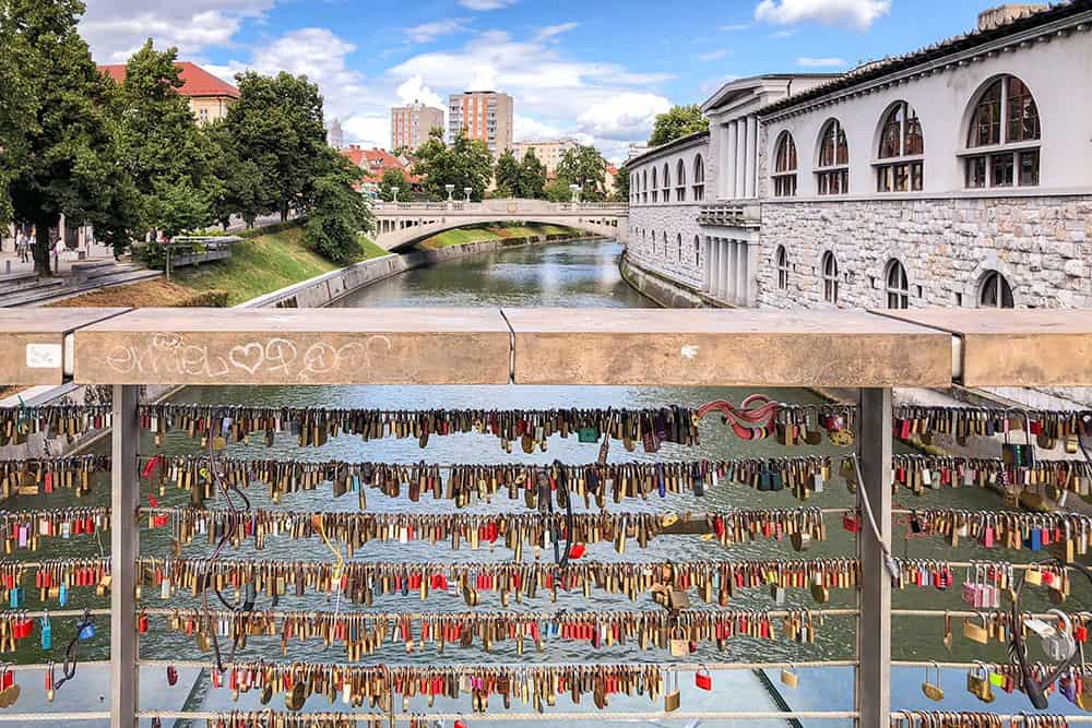 Bridge over the river with a lot of lovelocks on the railings