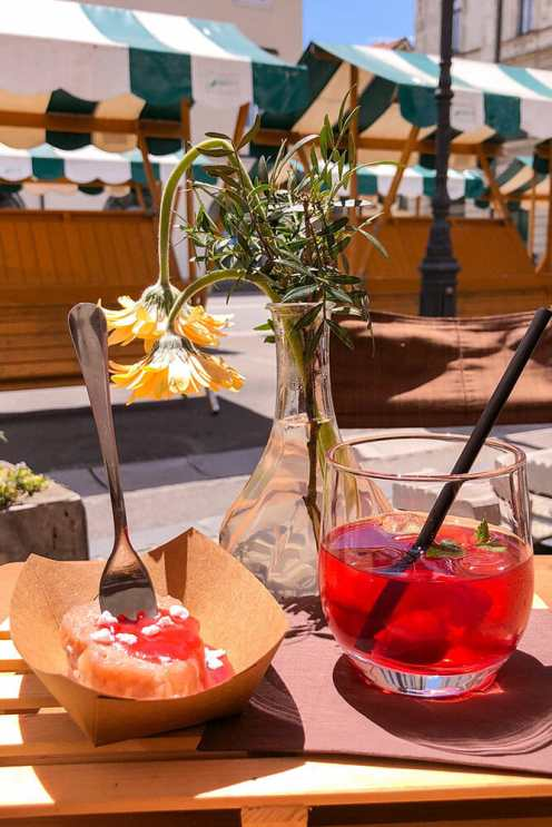 Dumpling with strawberry jam and red iced tea with a flower vase