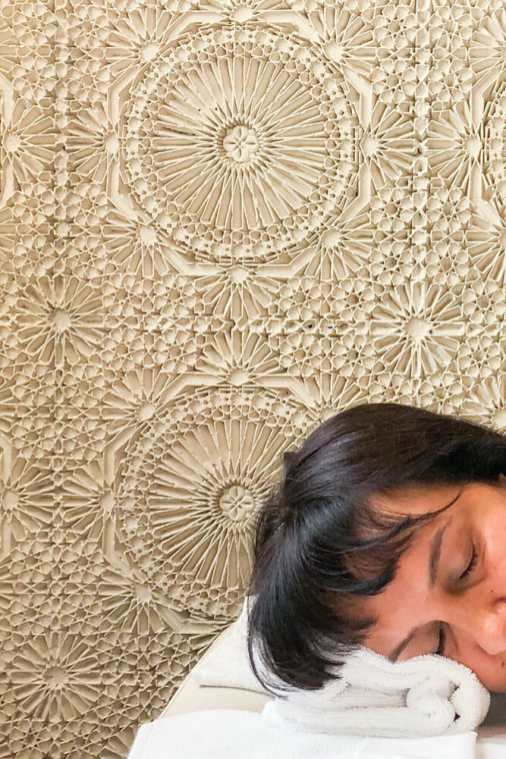 Head lying on a massage table with a white carved stucco wall in the background