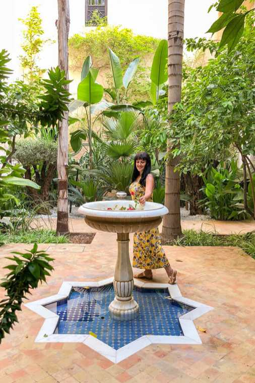 Standing by a fountain in a garden patio
