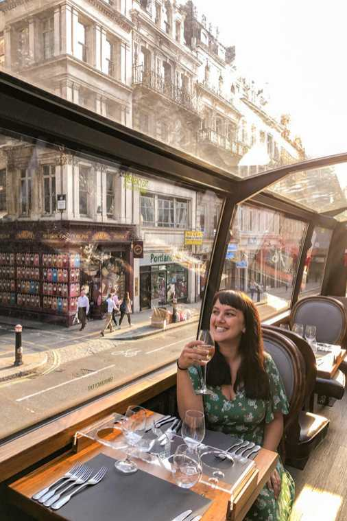 Sitting at a table for two for dinner while holding a glass of wine and enjoying the views of London from inside a glass roofed bus