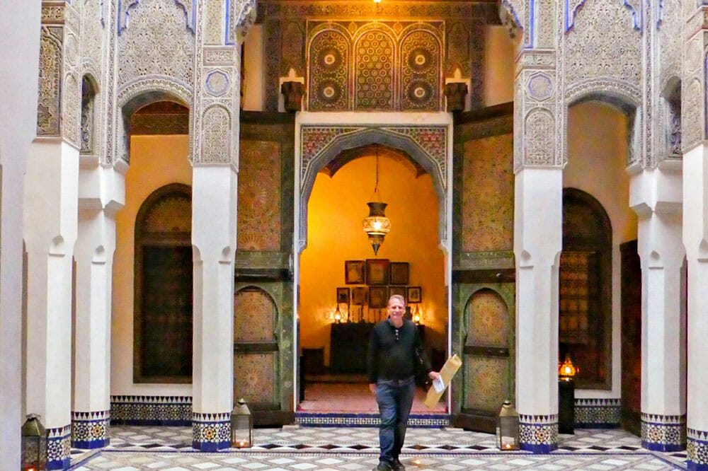 Standing in a courtyard decorated with columns, arches and colourful tiles