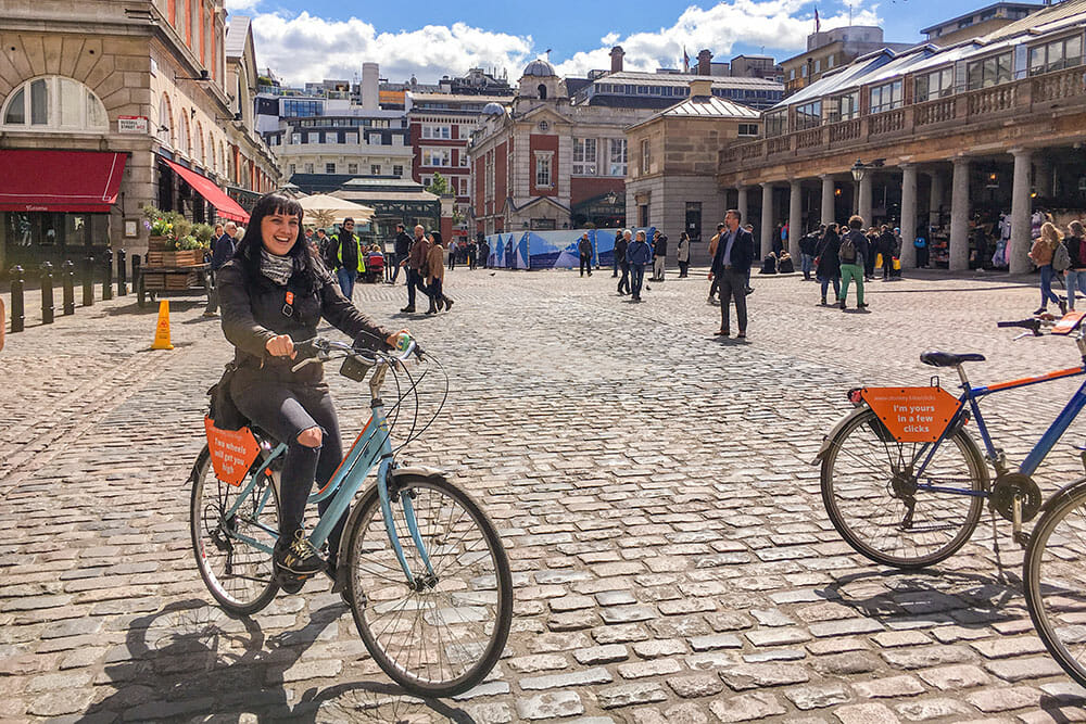 On a bike on the cobbles street of Covent Garden with buildings in the background