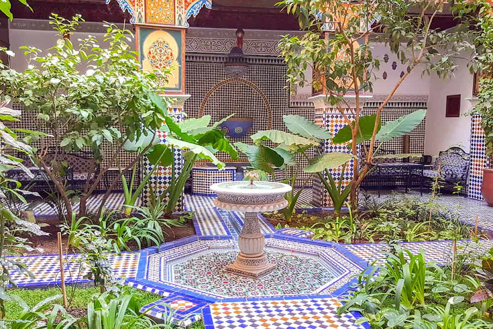 Courtyard decorated with colourful tiles with a fountain in the middle and plants around it