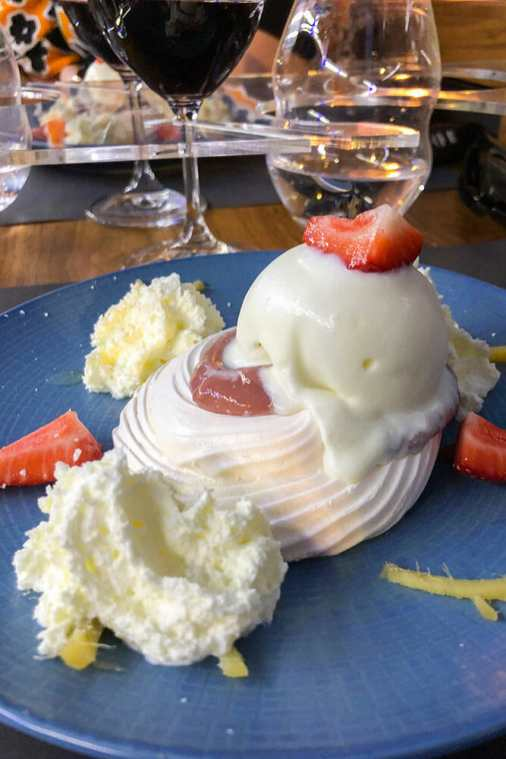 Strawberry and ginger pavlova with ice cream on top and cream on the side, all arranged on a blue plate