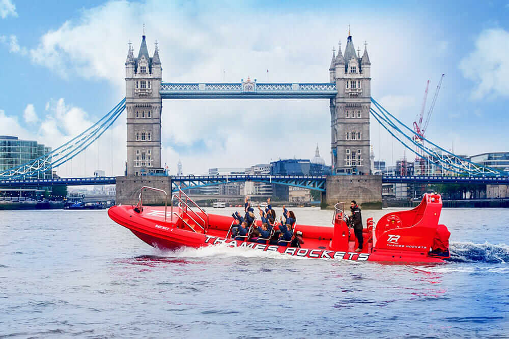 Red RIB speedboat making a turn in the river by Tower Bridge in London