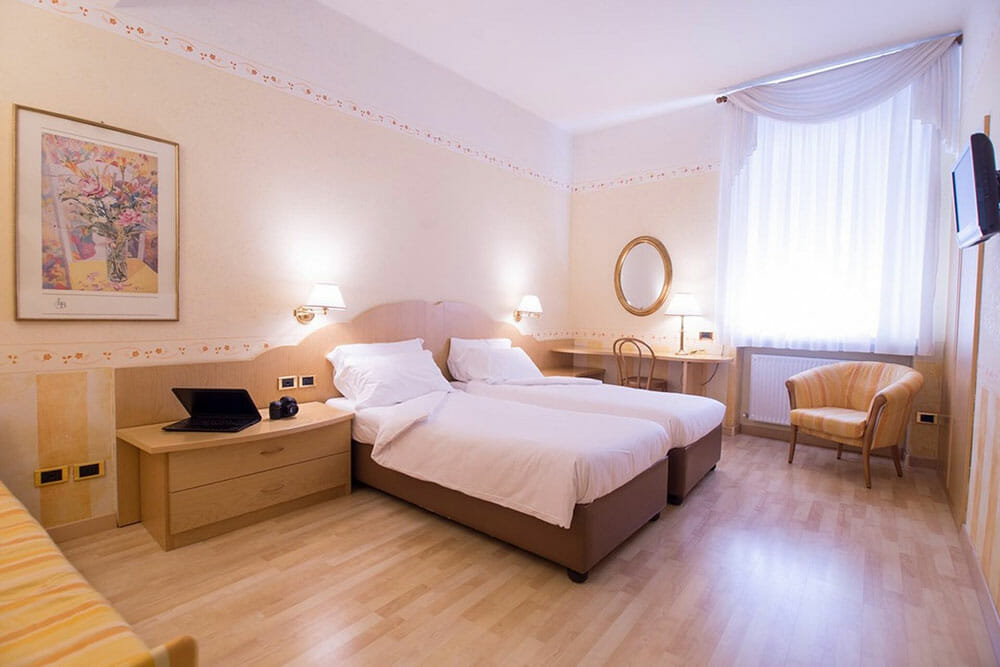 Spacious room with twin beds decorated in a cream colour