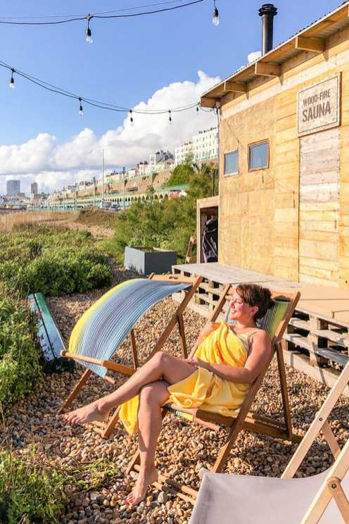Sitting on a deck chair wrapped in a yellow towel outside a wooden sauna box