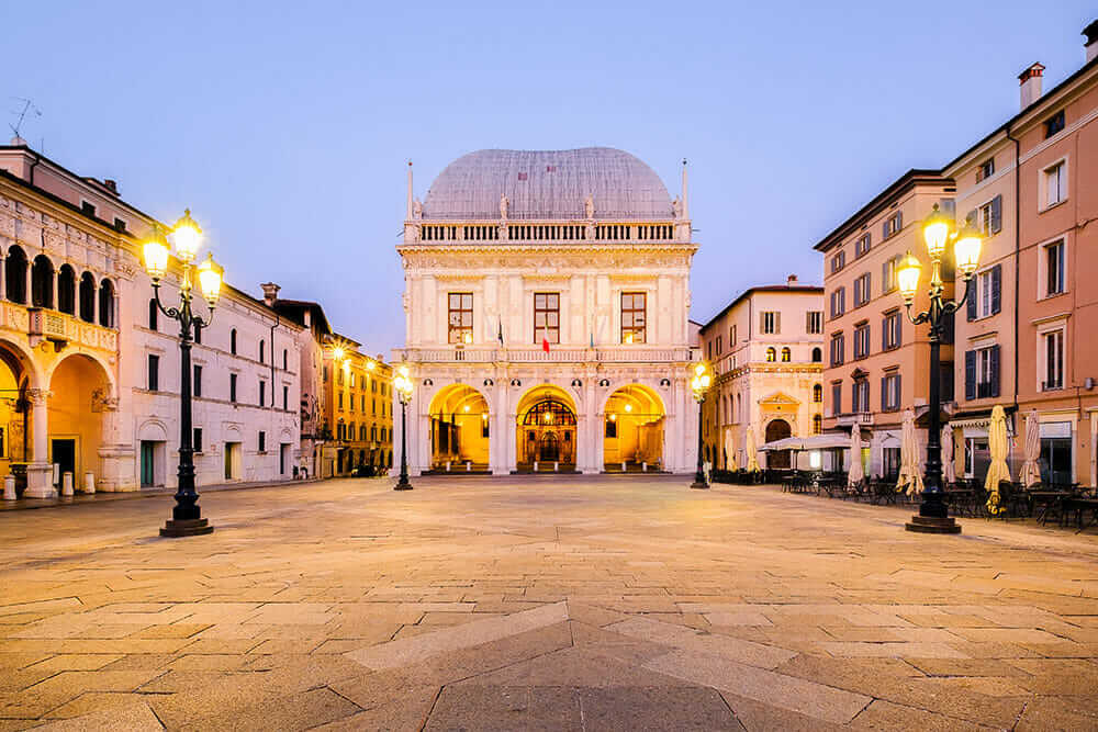 Italian Square with a grand building in the background and ornate street lights at dusk