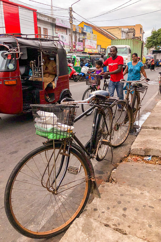 Street scene with a parked bicycle and a family pushing their bicycle next to a tuk tuk