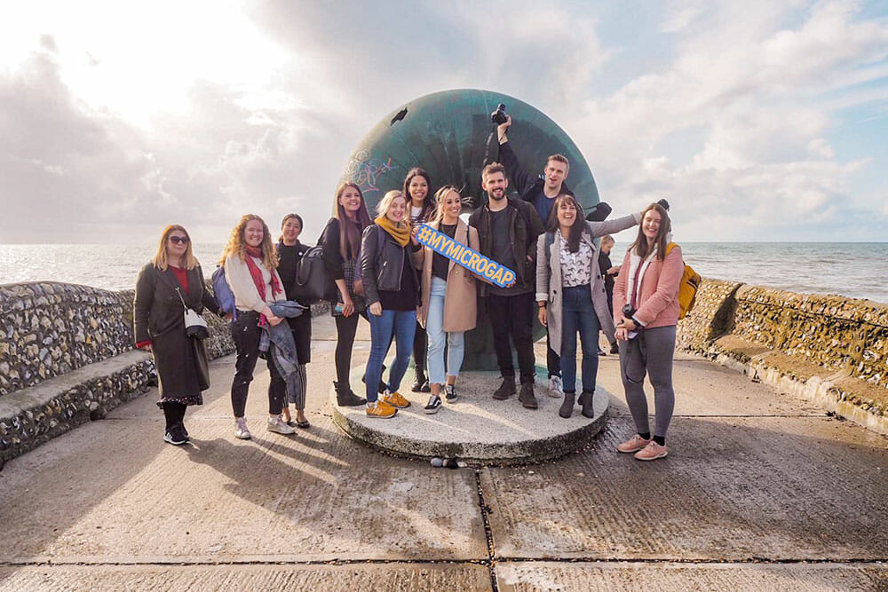 Group photo of eleven pope with a doughnut shape sculpture and the sea in the background