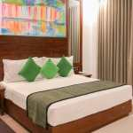 Hotel room with a large bed with green cushions and colourful artwork on the wall