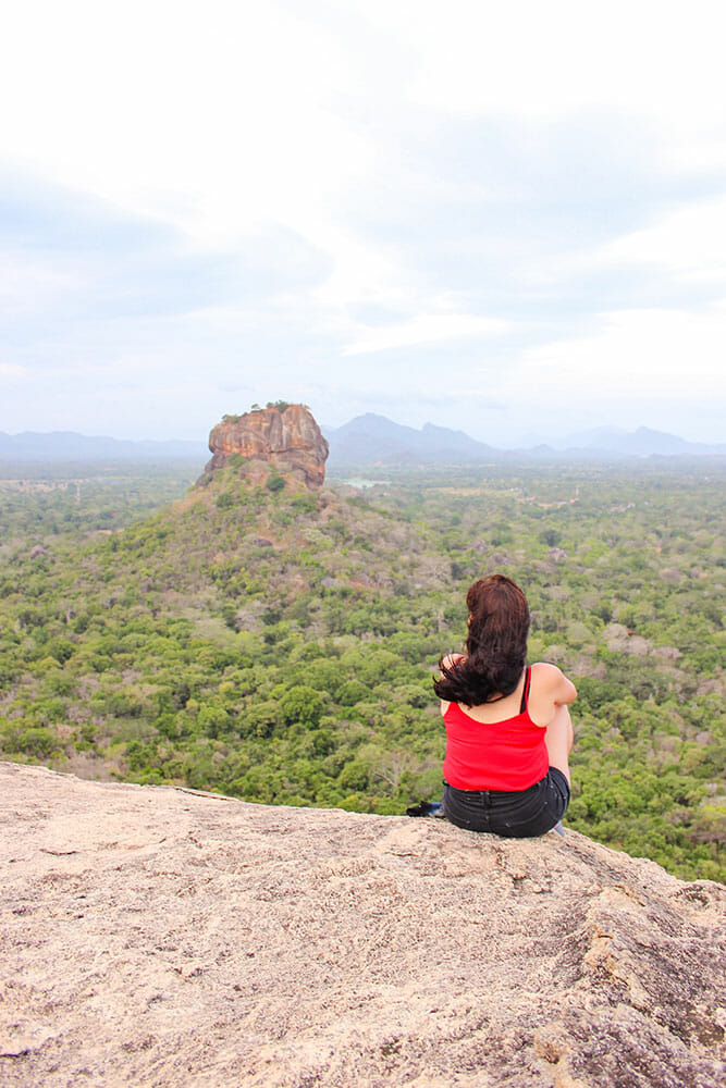 Sitting on a rock with a view of the jungle and a rocky outcrop in the distance
