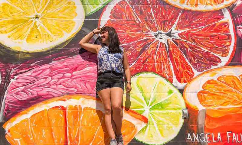 Standing in front of a wall mural of sliced citrus fruits in St Pete Florida
