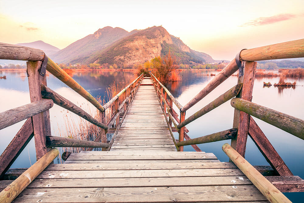Wooden pontoon built over a lake with the mountains in the background at sunset