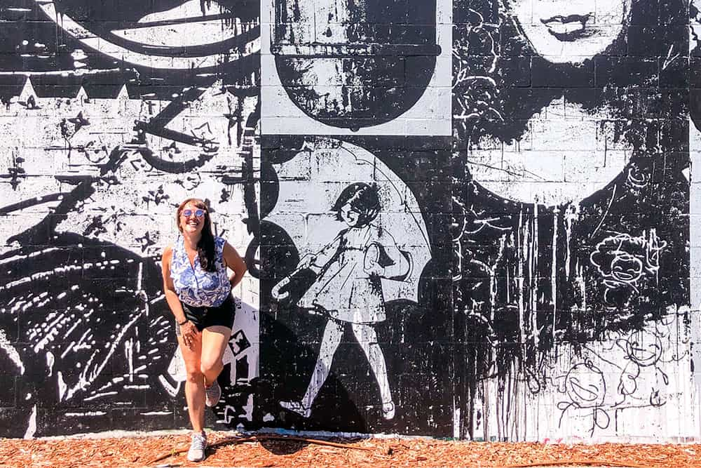Woman standing in front of a black and white mural showing a girl with an umbrella. Exploring the street art is how to spend a day in St Pete Florida