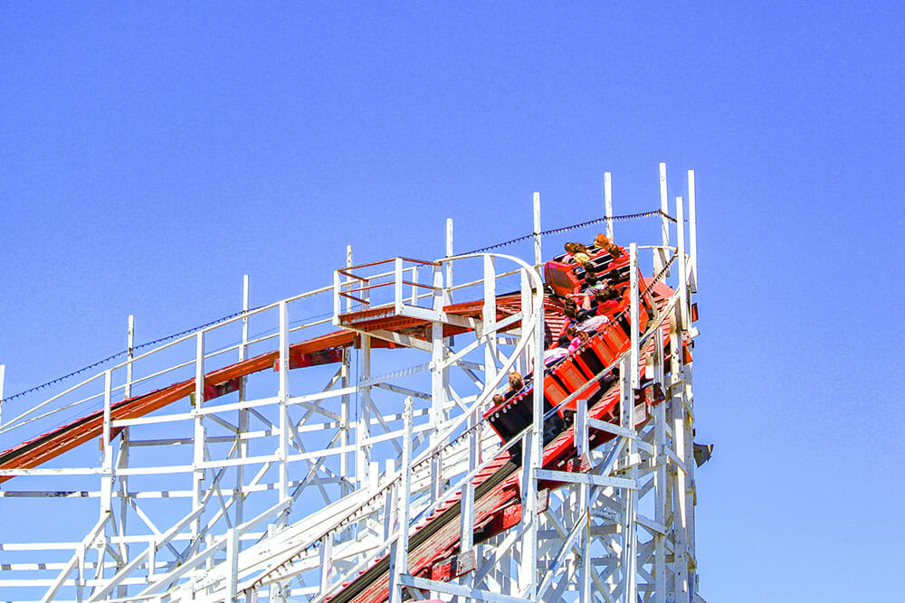 Wooden roller coaster with a red train going through