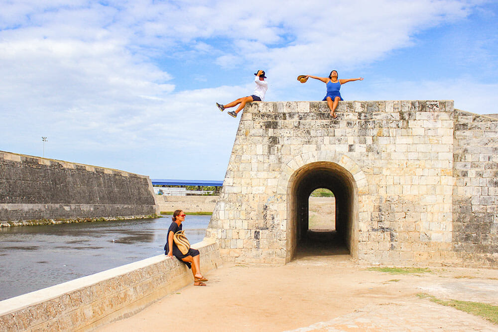 Two women and one man sitting on top of Jaffna Fort walls with a tunnel going through one of the walls and the moat on one side