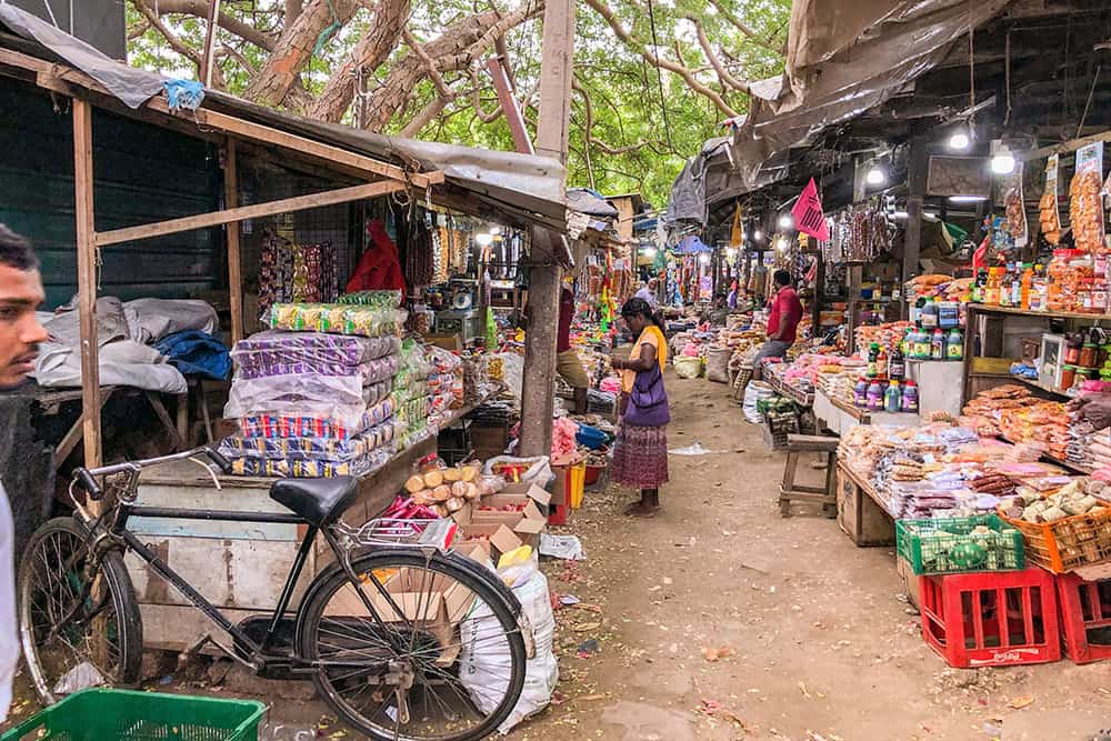 One of the top things to do in Jaffna is visiting Jaffna Market. Street market with shops selling local produce and a woman shopping.