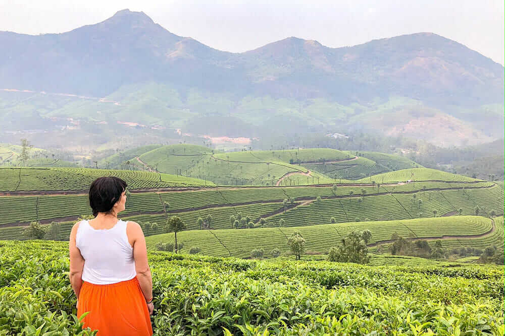 Woman standing in the middle of a tea plantation with views over the hilly tea plantation and the mountains further away