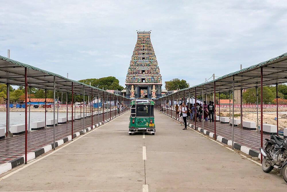 Tuk tuk driving down a straight road towards a hindu temple