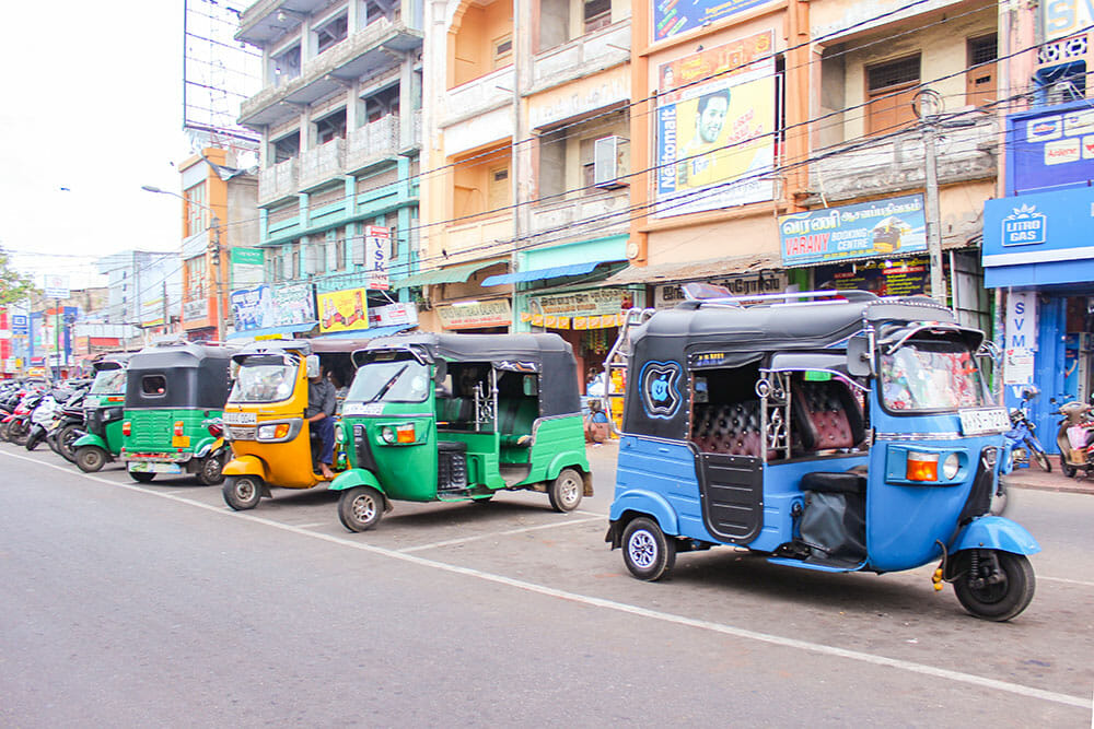 Line of colourful tuk tuks parked on the road with tall buildings behind them