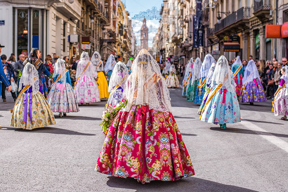 Parade of fallers, ladies dressed in the traditional dress of Valencia. This guide to las fallas tells you where to see them