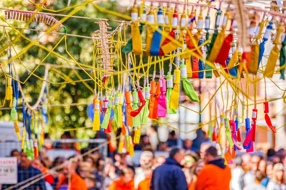 Dozens of colourful firecrackers tied to strings arranged with a crowd in the background waiting for the mascleta to go off