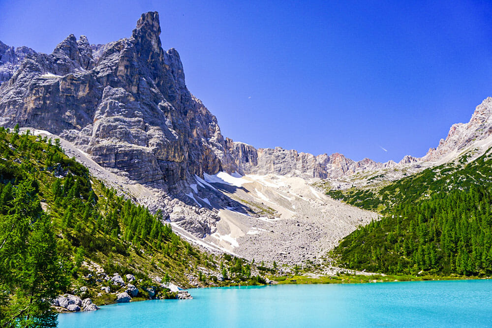 Blue water lake with a sharp mountain peak and alpine trees on the shore. This is another of the best hikes in the Dolomites