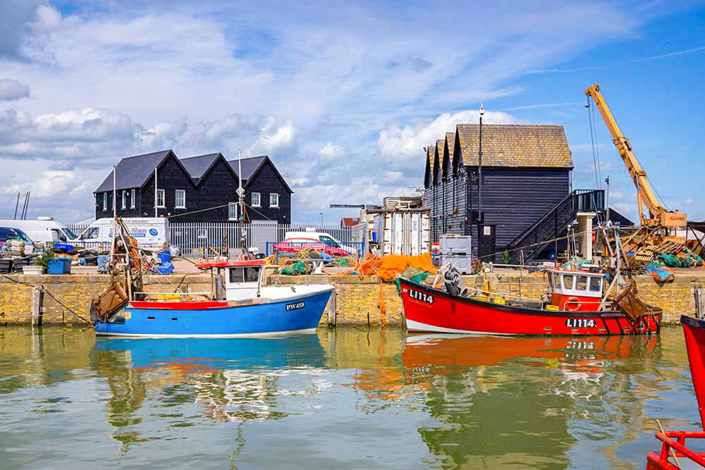 Fishing boats in the harbour with black oyster shack in the background