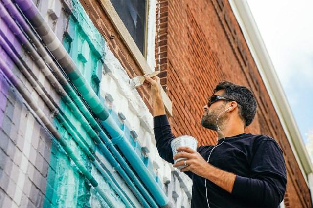 Gibbs Rounsavall working on his mural. (Courtesy Access Ventures)
