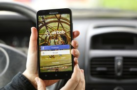 Novi Sad, Serbia - March 24, 2016: Close-up of an unrecognizable woman using the Airbnb App on her Lenovo A916 Android smartphone in a car. Login screen with Facebook and Google sign up options. Airbnb is a service for people to list, find, and rent lodging. It currently has over 1,500,000 listings in 34,000 cities and 190 countries.