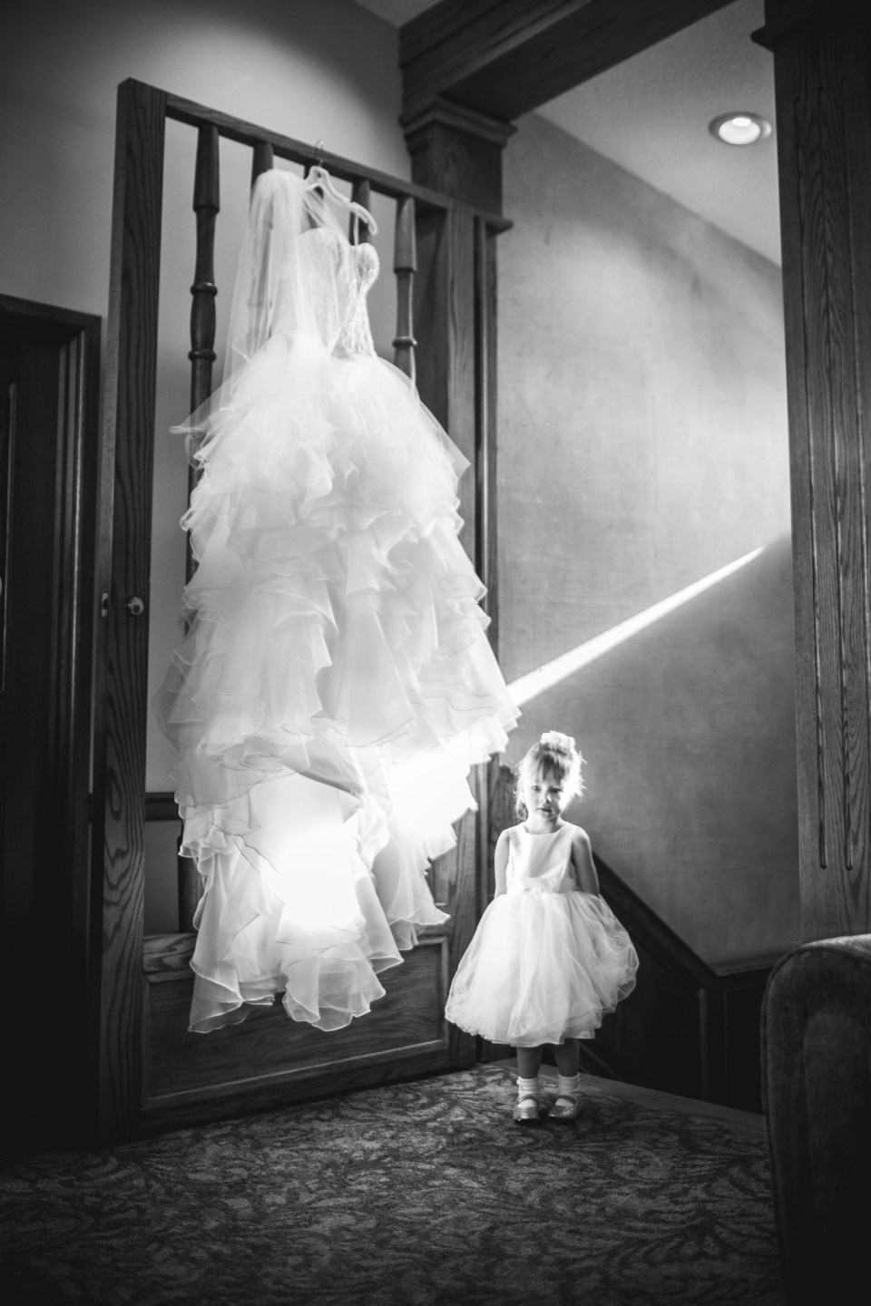 flower girl next to hanging wedding dress