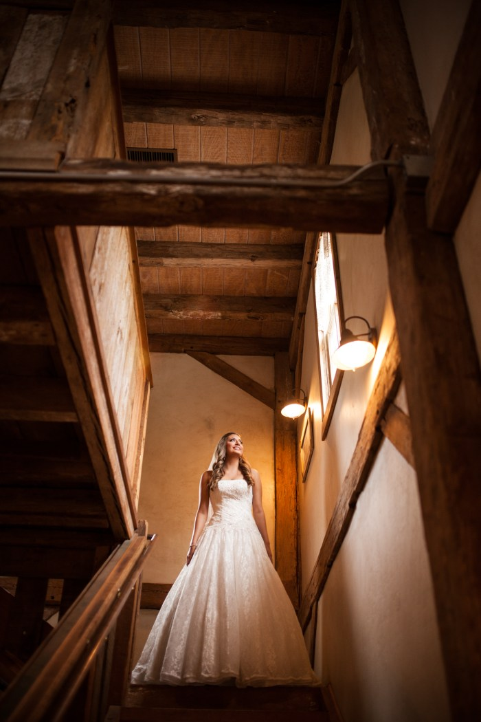 bride in rustic wooden barn looking out the window