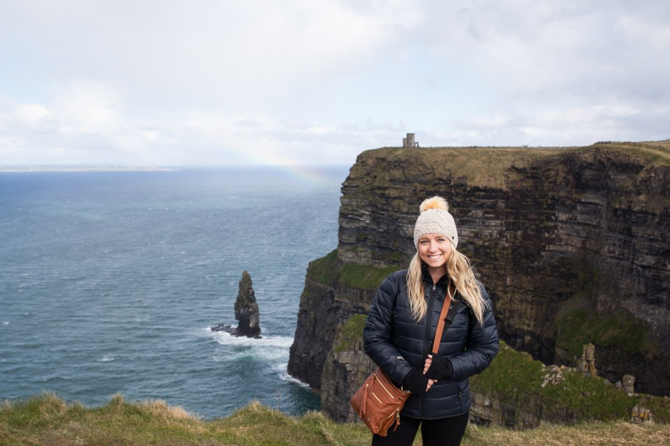 Brooke at the cliffs of Moher with rainbow