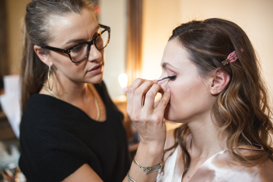 bride getting makeup done on wedding day