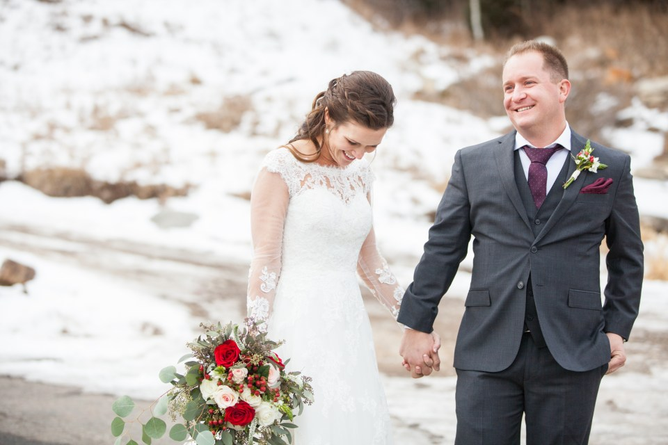 Durango, Colorado Winter Wedding ideas bride and groom in the snow with red rose bouquet and boutonniere