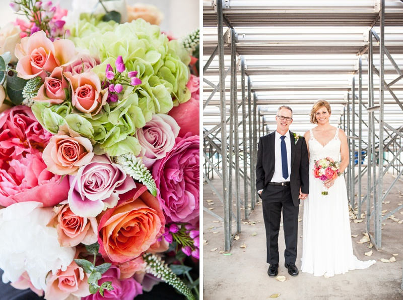 bride and groom behind bleachers at baseball wedding and colorful bouquet flowers