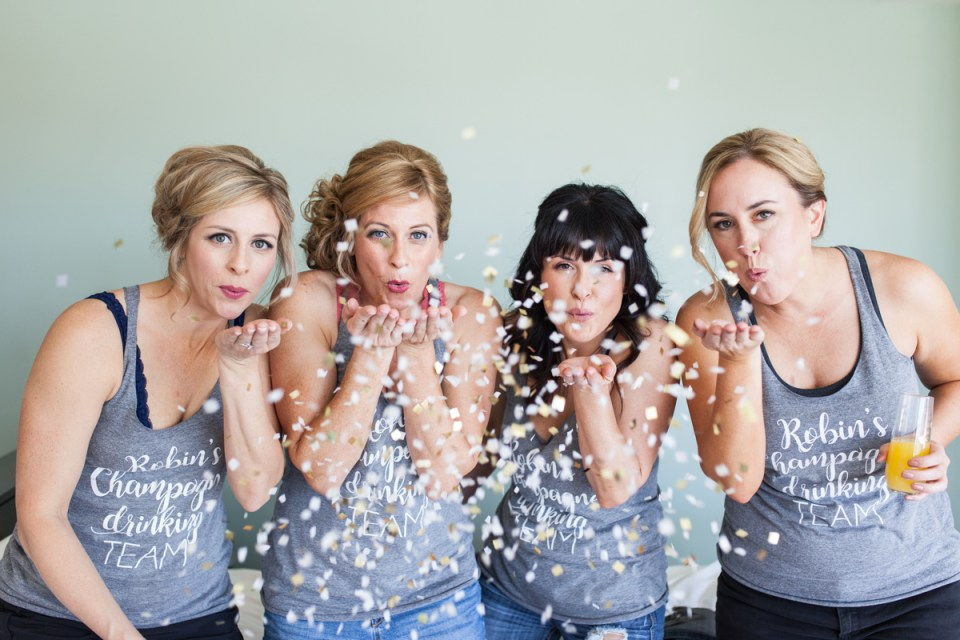 bride and bridesmaids throwing confetti on wedding day