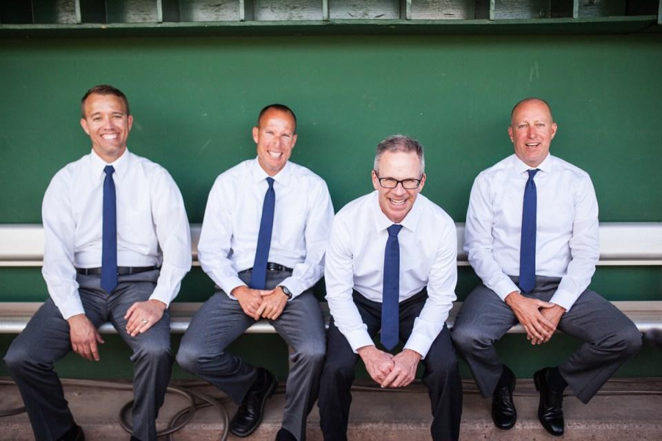 groom and groomsmen in dugout of baseball stadium