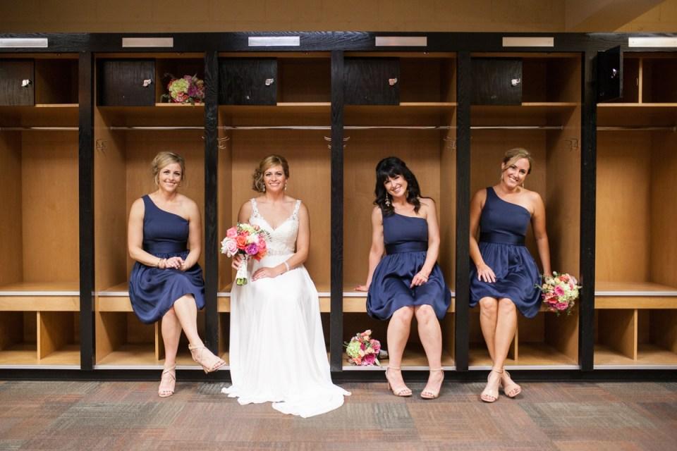 bride and bridesmaids in baseball locker room